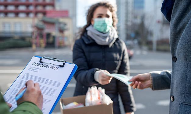 mujer repartiendo mascarillas en la calle